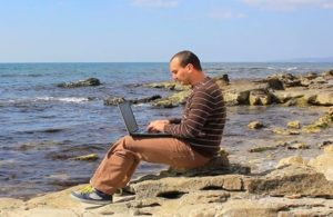 man working with laptop on a rocky beach